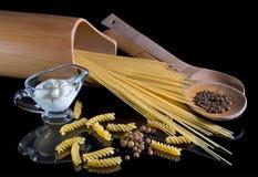 Pasta italiana gialla, spaghetti, pepe nero contro i precedenti isolati neri Una bella natura morta r fotografie stock