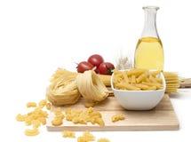 Pasta italiana, spolette dei maccheroni con i pomodori ciliegia e olio d'oliva in una bottiglia di vetro Immagini Stock