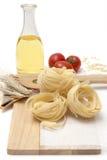 Pasta italiana, tagliatelle dei maccheroni con i pomodori ciliegia e olio d'oliva in una bottiglia di vetro Immagine Stock