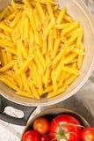 Pasta italiana in un filtro con una tazza dei pomodori su Libro Bianco fotografia stock