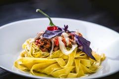 Pasta italiana in un piatto in un ristorante con i peperoncini rossi Immagine Stock
