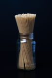 Pasta in Jar. Uncooked spaghetti noodles in jar on black background Stock Photos