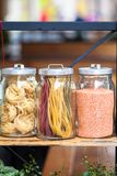 Pasta in the jar. On kitchen shelves are different kinds of pasta in glass jars royalty free stock photography