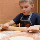Pasta joven del balanceo del muchacho con un rodillo de madera grande como él prepara las tortas Imágenes de archivo libres de regalías