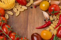 Pasta, kryddor och körsbärsröda tomater på träbräde Arkivbilder