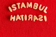 Pasta placed to spell words istambul and hatirasi. Pasta letters placed to spell words istambul and hatirasi sitting on top of bright red table surface royalty free stock photos