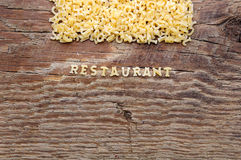 Pasta letters on wooden background Royalty Free Stock Images
