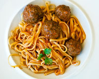 Pasta Linguine with meatballs and tomato sauce. Italian food. Delicious pasta Linguine with meatballs and tomato sauce, served on a white plate. Upper view Stock Photos