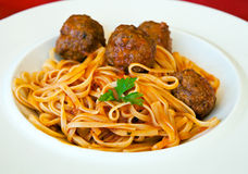 Pasta Linguine with meatballs and tomato sauce. Italian food. Delicious pasta Linguine with meatballs and tomato sauce, served on a white plate.  Close up Stock Images