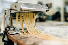 Pasta machine with dough closeup, nobody. Pasta machine with dough on wooden kitchen table sprinkled with flour closeup, nobody. Traditional italian cuisine Royalty Free Stock Photography