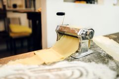 Pasta machine with dough on wooden kitchen table. Sprinkled with flour, nobody. Traditional italian cuisine Stock Photos