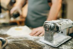Pasta machine, male chef preparing dough. On wooden kitchen table. Homemade spaghetti cooking Stock Images