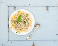 Pasta mafaldine with mushrooms and cream sauce in white ceramic plate over light blue wooden background. Top view. Stock Image