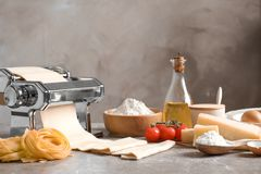Pasta maker with dough and products. On kitchen table Royalty Free Stock Image