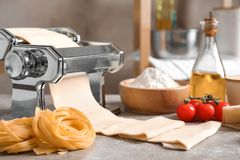 Pasta maker with dough and products. On kitchen table Stock Photo