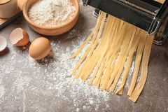 Pasta maker with dough and products. On kitchen table Royalty Free Stock Photography