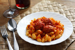 Pasta with meat balls. Bend tubes pasta with tomato sauce and meat balls on white plate Royalty Free Stock Images