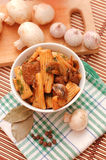 Pasta with meat and mushrooms. In a round white plate on the kitchen table Royalty Free Stock Images