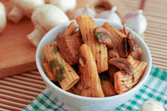 Pasta with meat and mushrooms. In a round white plate on the kitchen table Stock Photography
