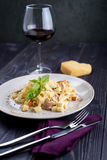 Pasta with meat and mushrooms on a plate and a glass of wine stock photography
