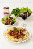 Pasta with meat sause, green salad and wine. On white background Stock Image