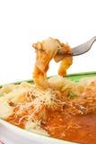 Pasta med Bolognese sås på en gaffel över en platta Arkivfoto