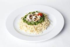Pasta med champinjoner och körsbärsröda tomater som fodras av en cirkel av grönskacloseupen Arkivfoton
