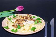 Pasta med champinjoner p? en m?rk bakgrund arkivfoton