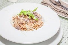 Pasta med champinjonsås och grated parmesan Arkivfoto