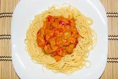 Pasta med en sås av hemlagad höna, söt peppar, moroten och nya tomater arkivbild