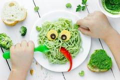 Pasta med grön grönsakpesto formade det sunda gulliga monstret - Arkivfoto