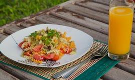 Pasta med grönsaker och ett exponeringsglas av ny orange fruktsaft Royaltyfri Bild