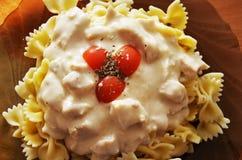 Pasta med höna- och ostsås, körsbärsröda tomater royaltyfri bild
