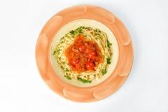 Pasta med körsbärsröda tomater, zucchinin och letcho på en vit bakgrund arkivbild