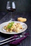 Pasta med kött och champinjoner på en platta och ett exponeringsglas av vin arkivbild