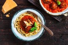 Pasta med köttbullar och tomatsås och ost, bästa sikt, lantlig stil arkivbild