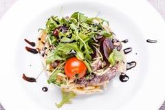 Pasta med nötkött och druvor i en vit platta Arkivfoto