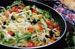 Pasta med oliv och tomater Arkivbild