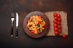 Pasta med ost, den körsbärsröda tomaten, gaffeln och kniven på rostig bakgrund fotografering för bildbyråer