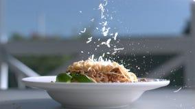 Pasta med ostplattan som sitter på en tabell och en parmesan, faller på basilika och spagetti i ultrarapid lager videofilmer