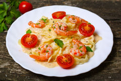 Pasta med räka, tomater, örter och kräm- sås Arkivfoto