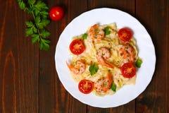 Pasta med räka, tomater, örter och kräm- sås Arkivfoton