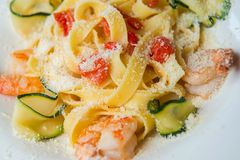 Pasta med räkor, zucchinin, tomater och parmesan fotografering för bildbyråer