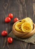 Pasta med tomaten på en träbakgrund Arkivbild
