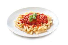 Pasta med tomatsås och basilika – 'lurar Penne al Pomodoro Basilico 'på vit bakgrund royaltyfri foto