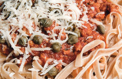 Pasta with minced meat, capers and parmesan cheese. Whole wheat pasta with minced meat, capers and parmesan cheese Stock Images