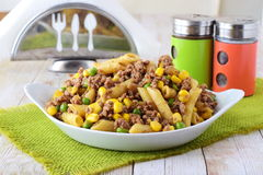 Pasta with minced meat, green peas and yellow corn in a white plate. Home cooking. Healthy eating concept. Stock Image