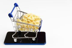 Pasta with mini cart supermarket on a smartphone, on white background. Concept of delivery, online shopping. Copy space royalty free stock photos