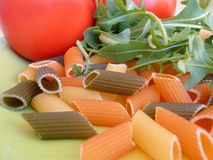 Pasta multi colored. Red, green, yellow pasta with tomato and parsley Royalty Free Stock Photography