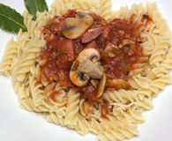 Pasta with Mushrooms. Fusilli pasta with mushrooms and bacon in tomato sauce Stock Photo